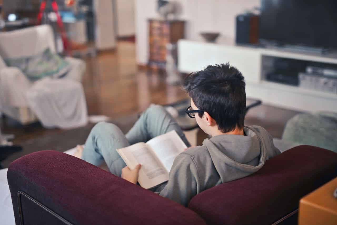 Ein Student sitzt in seiner ersten eigenen Wohnung auf dem Sofa.